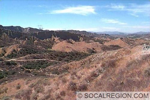 Overview of Vasquez Canyon. These hills are composed of the Mint Canyon Formation. Saugus is visible as a green area in the middle right background.