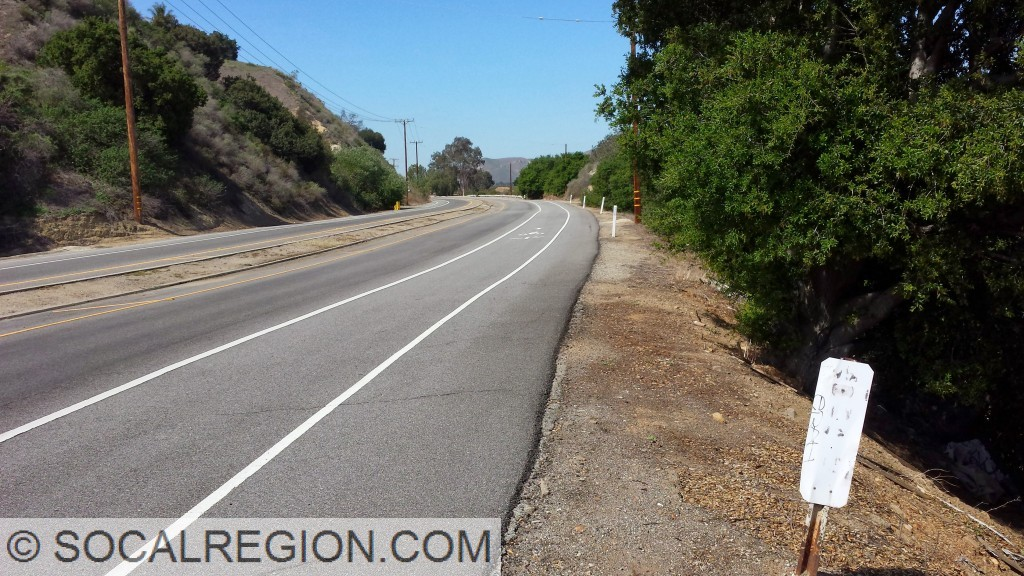 Section of Palisades Drive, restriped to two lanes from four. Old raised median and wooden railing are visible here.